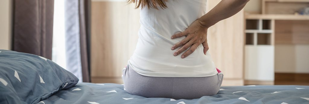 woman sitting on bed holding sore lower back